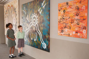 Two students st St Francis Xavier's Catholic Primary School Lurnea admiring Indigenous murals on school grounds