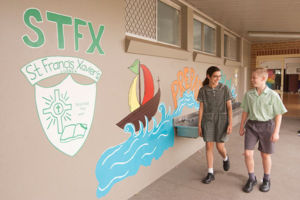 Two students at St Francis Xavier's Catholic Primary School Lurnea walking and smiling in front of mural