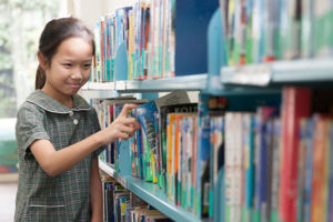 St Francis Xavier's Catholic Primary School Lurnea student selecting book in school library