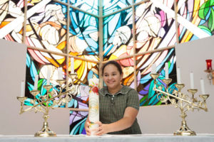 St Francis Xavier's Catholic Primary School Lurnea student smiling and placing candle on altar in church