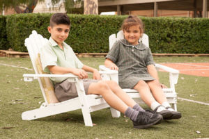 Students sitting and smiling in lawn chairs at St Francis Xavier's Catholic Primary School Lurnea